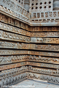 The base of the temple walls consist of moldings with friezes that consist of (from bottom to top) elephants, lions, scrolls, horses, scrolls, puranic scenes, mythical beasts (makara) and swans at Hoysaleshwara temple in Halebidu