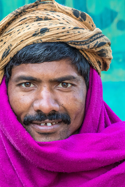 Beda, Bhoramdeo, Chhattisgarh, India. A young Baiga villager wards off the morning chill with a bright wrap.
