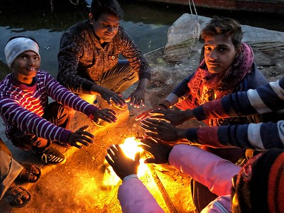 Keeping warm in Varanasi  on the steps next the the Ganges River!