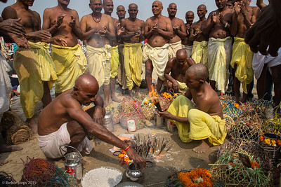 The holy men are blessing the many containers of holy water from the Ganges River after the ritual bathing in the morning.