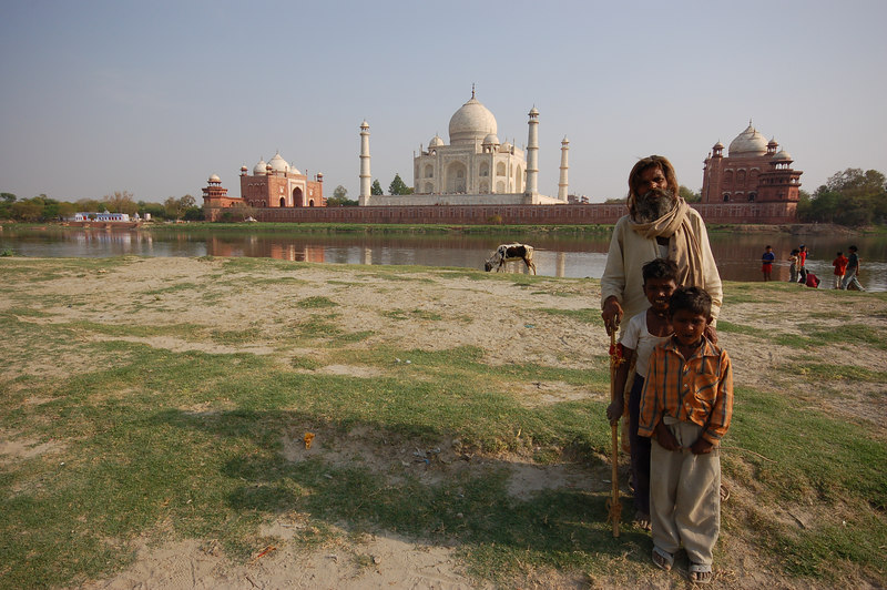 A shepperd and his sons posing in front of the Taj Mahal.