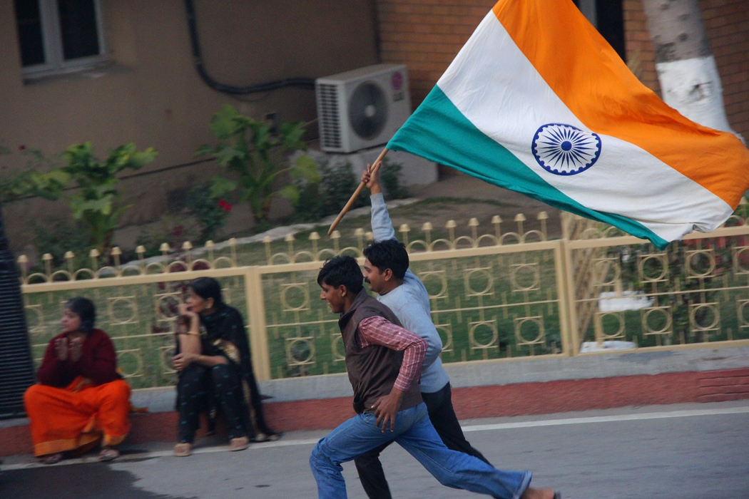 http://nomadicsamuel.com : Indian men running down the parading area with a flag from India before the border closing Ceremony between India and Pakistan in Wagah - travel photo