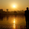 "A man standing still & observing the sunrise at the Harmandir Sahib (golden temple) located in Amritsar, Punjab - India.  Travel photo from Amritsar, India. <a href=""http://nomadicsamuel.com"">http://nomadicsamuel.com</a>"