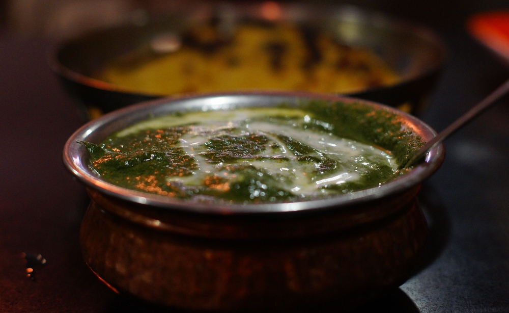 This is a travel photo of a delectable dish of creamy Palak Paneer, consisting of spinach & cheese cubes, at an Indian restaurant in Amritsar, India