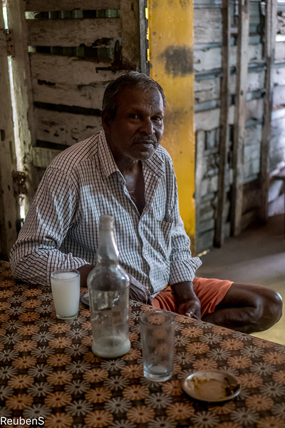 Man in the toddy shop drinking coconut beer.