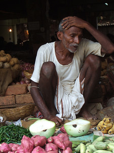 Elderly man selling his wares. He looks tired and unhappy.