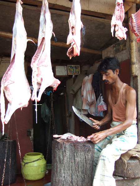 Butcher at the market. Tree trunk serves as the butcher's block. Young goats hanging in the foreground.