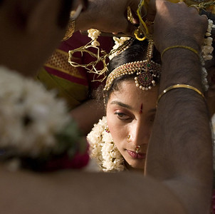 The groom is tying the Mangalsutra around the bride's neck. This necklace is the equivalent to a wedding ring.  Traditionally, a married woman never removed her mangalasutra. If she became a widow, it was cut off.