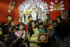 The whole family poses in front of their Durga idol.  A television crew was on hand to record the event.