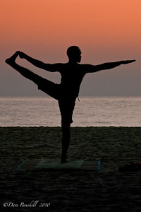 A man practices Yoga at sunrise on the beach at Patnem Beach, Goa, India