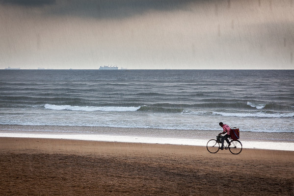 GOA, INDIA - OCTOBER 16, 2010: Boy speeding on bicycle under rain on beach (motion blur). Goa state is premier beach destination of India