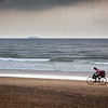 GOA, INDIA - OCTOBER 16, 2010: Boy speeding on bicycle under rain on beach (motion blur). Goa state is premier beach destination of India