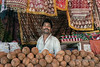 """Portrait of a shop keeper, Pavagadh Hill, Gujarat State, India<br /> <br /> I like how pleased he looks to have his photo taken,surrounded by his coconuts and beautiful fabrics. Note the single marigold among the coconuts.<br /> <br /> A photo of a decorated elephant, the Marahajah's palace, and other scenes can seen here: <a href=""""http://goo.gl/KCDsM8"""">http://goo.gl/KCDsM8</a><br /> <br /> 18/12/13  <a href=""""http://www.allenfotowild.com"""">http://www.allenfotowild.com</a>"""