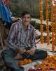 Man making marigold strings, Pavagadh Hill, Gujurat, India
