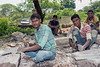 Stoone workers preparing flooring slabs for an unidentified arched building on the road to Pavagadh Hill that is undergoing restoration, Champaner-Pavagadh Archaeological Park, Gujarat, India