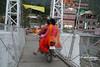 motorcycling across a pedestrian bridge.