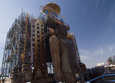 Devotees make their way up the scaffolding to pour their offerings over the head.