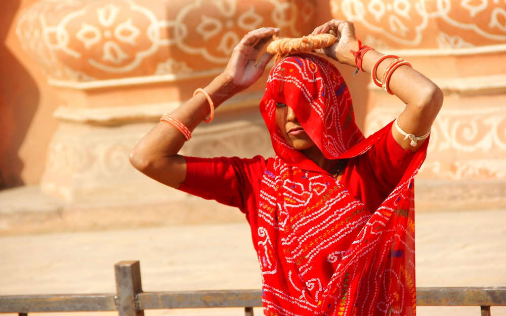 An India lady strolls down the street in her colourful and distinct red sari.