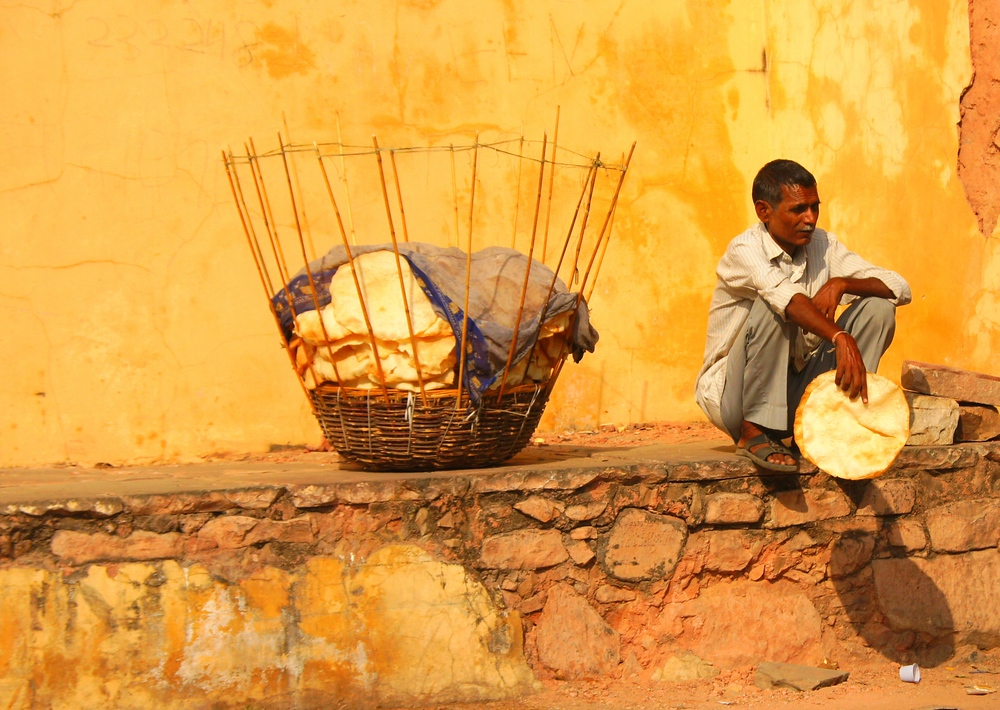 A man sits outside on the ledge with has basket of crispy flat-bread - Jaipur, India