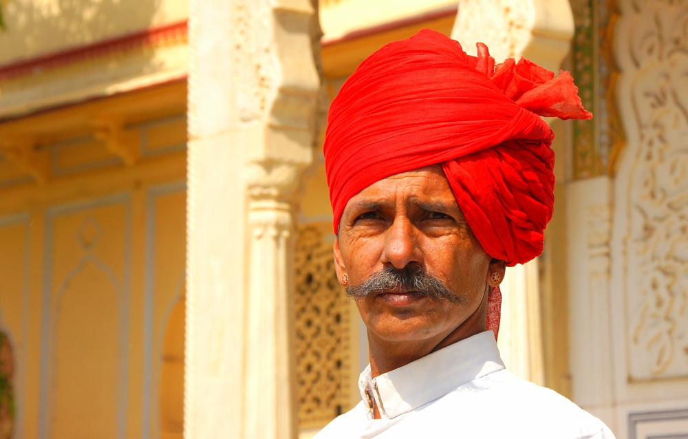 An Indian man with a distinct face and headdress posers at the Fort - Jaipur, India.