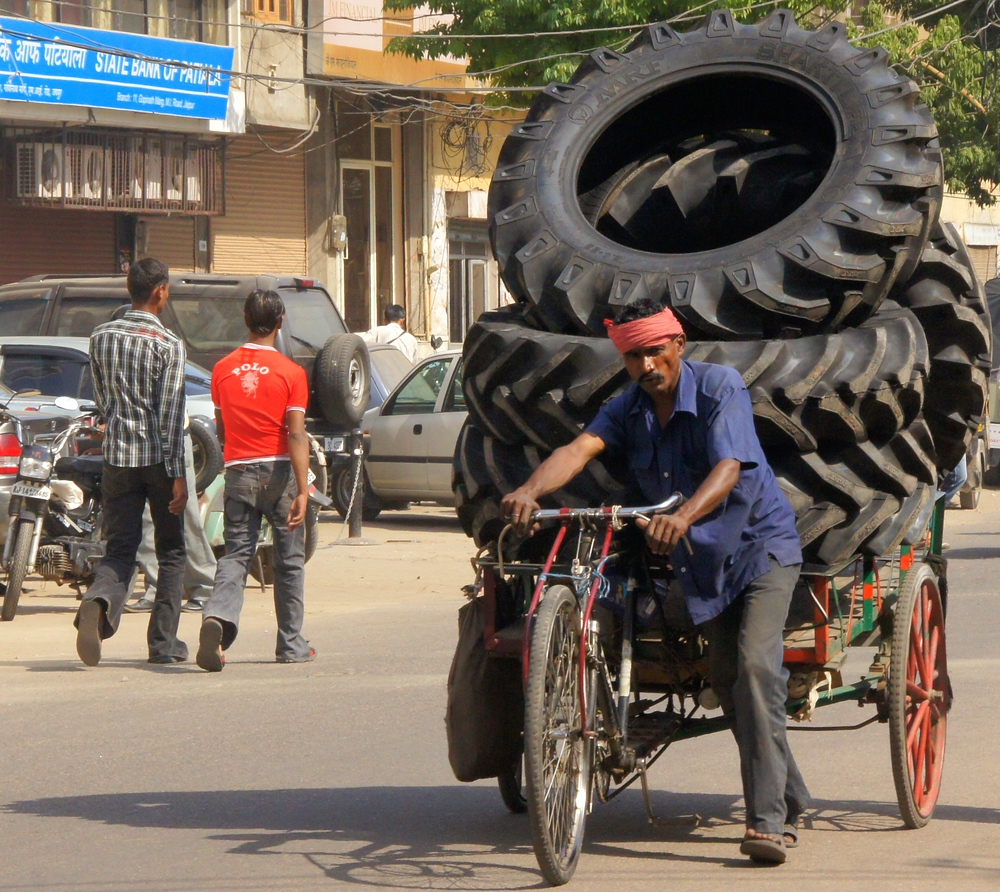 A man hauls and enormous load of tires on the back of his rickshaw.