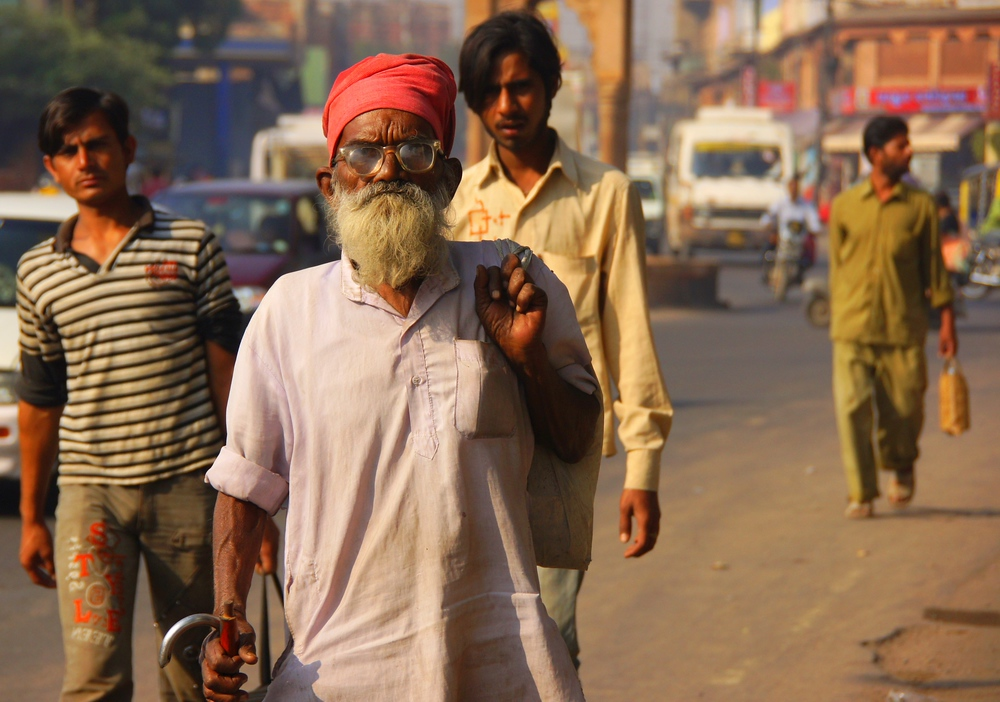 Today's daily travel photo is of a bearded Indian man wandering down a hectic section of Jaipur, Rajasthan, India in broad daylight.