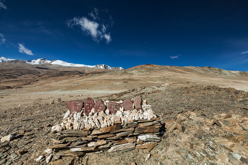 Stones with Tibetan Buddhist mantra at Himalayan lake Tso Moriri. Korzok,  Changthang area, Ladakh, Jammu and Kashmir, India
