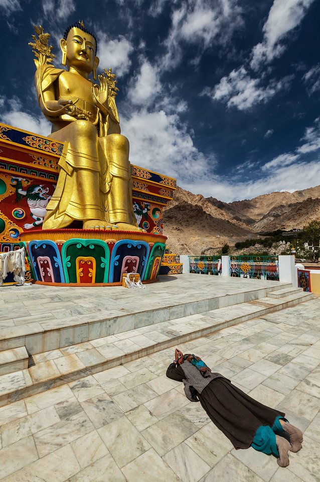 Tibetan Buddhist woman worshiping Buddha, Ladakh
