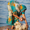 Indian woman performs morning pooja on holy river Narmada ghats