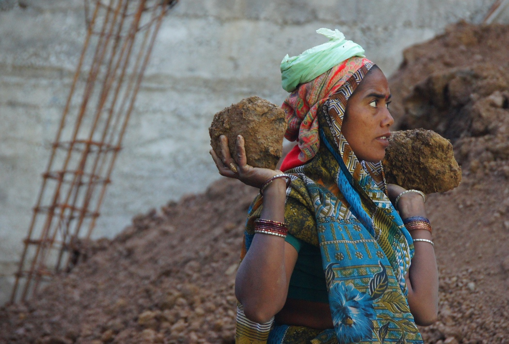 An India lady carrying large rocks at a construction site - Mcleod Ganj, India.  This is as a travel photo from Mcleod Ganj, India.
