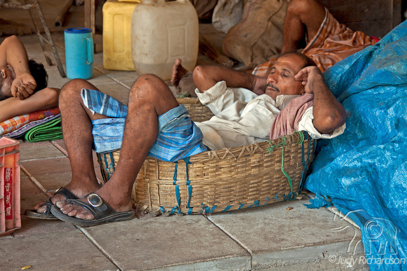 Man fits into basket for a nap at Crawford Market on a Sunday, in Mumbai, India.