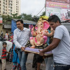 Men carrying a Ganesh statue, Mumbai, India<br /> <br /> Ganesh Chaturthi (Elephant God Festival) is a 10 day festival celebrating the elephant headed god Ganesha. Colourfully decorated Idols of Lord Ganesha are installed in homes and are paraded down the street accompanies with lively and enthusiastic songs, dances and drum beats.<br /> <br /> Lord Ganesha is considered to be the remover of obstacles and the also the Lord of letters and learning.  As such, he is a the patron of the arts and sciences and of intellect and wisdom.