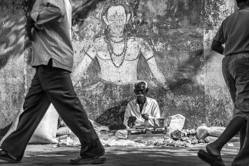 Street vendor under the image of a Hindu deity, Banganga Tank