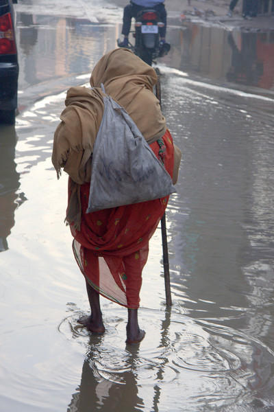 Paharganj, New Delhi, feb 2011;  An Elderly lady is bearfoot and this is a lot more than just water!
