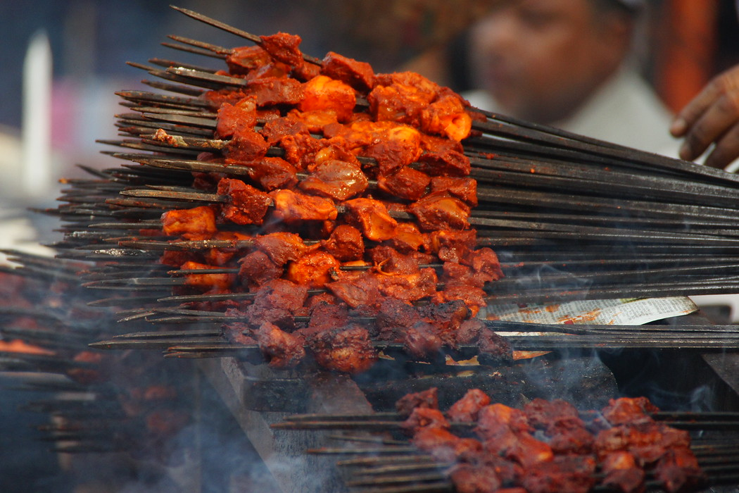 Smoking satay being offered up to large crowds forming outside the Jama Masjid - Old Delhi, India.  This is a travel photo from Old Delhi, India.