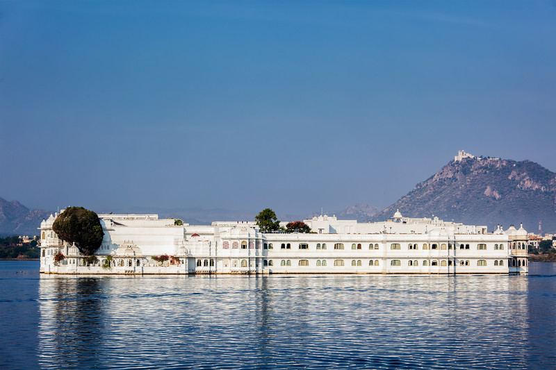 "UDAIPUR, INDIA - NOVEMBER 23, 2012: Lake Palace (Jag Niwas) in Lake Pichola, Udaipur, Rajasthan. Lake Palace is a famous luxury hotel and has been voted as the most romantic hotel in India and in the world. Was featured in James Bond film ""Octopussy""  as the home of titular character"