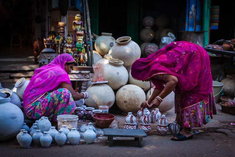 Rajasthani women painting pots in street. Jodhpur, Rajasthan, India