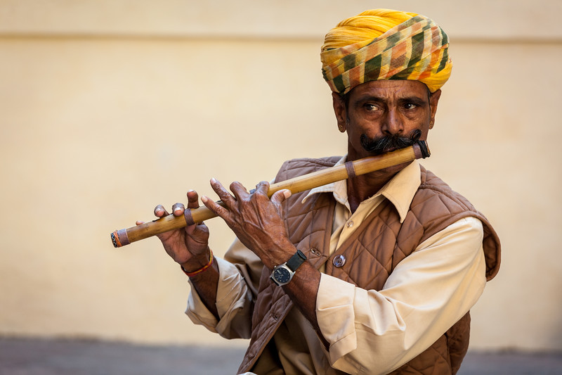 Indian man plays wooden flute in Mehrangarh fort