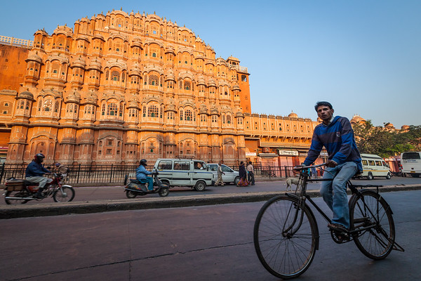 Unidentified Indian man driving bicycle in front of  Hawa Mahal palace in Jaipur, Rajasthan, India