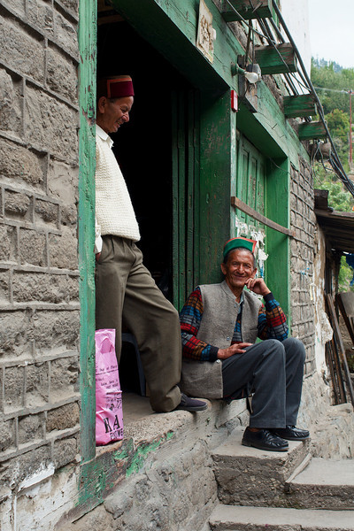 Kalpa villagers sit on the steps of a local store
