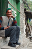 A Kalpa villager sits on the steps of a local store