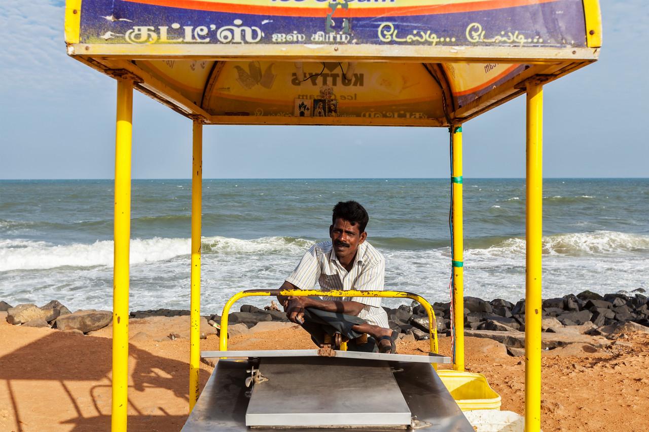 PONDICHERRY, INDIA - FEBRUARY 2, 2013: Unidentified Indian street ice cream vendor with cart on beach
