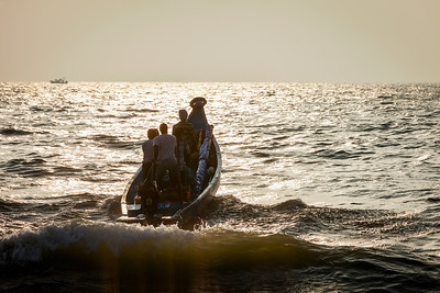 CHENNAI, INDIA - FEBRUARY 10, 2013: Group of Indian fishermen going into the sea on boat for fishing on sunrise