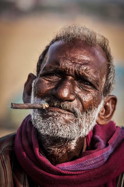 Old fisherman smoking on Marina beach in Chennai, Tamil Nadu, India