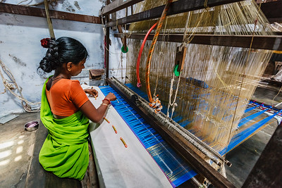 KANCHIPURAM, INDIA - SEPTEMBER 12, 2009: Woman weaving silk sari on loom. Kanchipuram is famous for hand woven silk sarees and most of the city's workforce is involved in  weaving industry