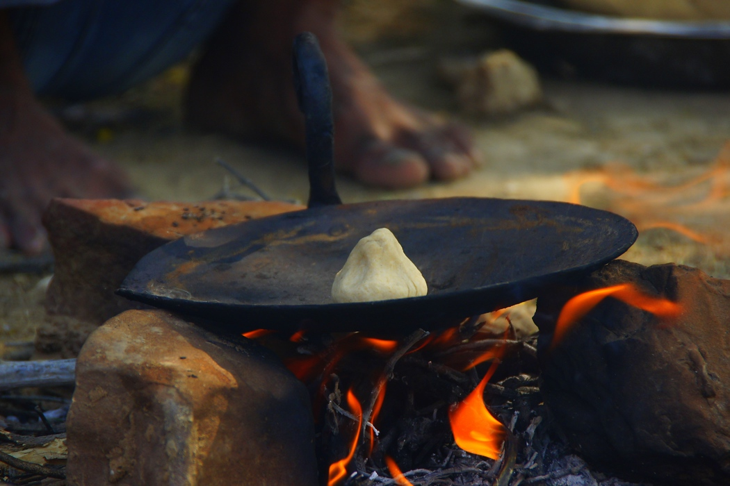 Cooking over an open camp fire to make a chapati for lunch.  Travel photo from the Thar desert camel safari tour in Jaisalmer, Rajasthan - India.