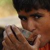 """Camel tour guide's nephew drinking a cup of Chai on our Thar Desert safari - Thar Desert, India.  This is a travel photo from the Thar Desert, India. <a href=""""http://nomadicsamuel.com"""">http://nomadicsamuel.com</a>"""