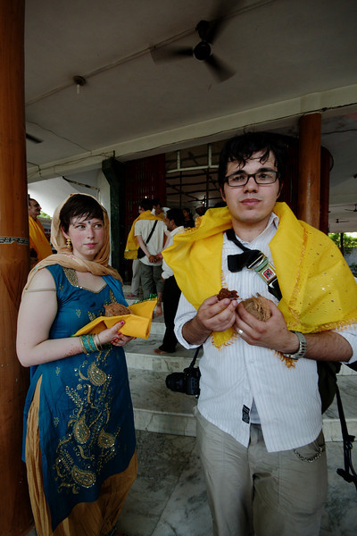 Antonia and James with their yellow stoles and coconuts, gifts from the Sai Baba Temple