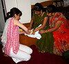 Lucie places a hand print on a white stole that Jitendra will wear during the wedding ceremony