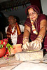 Jitendra's mother grinds grains during the ceremony